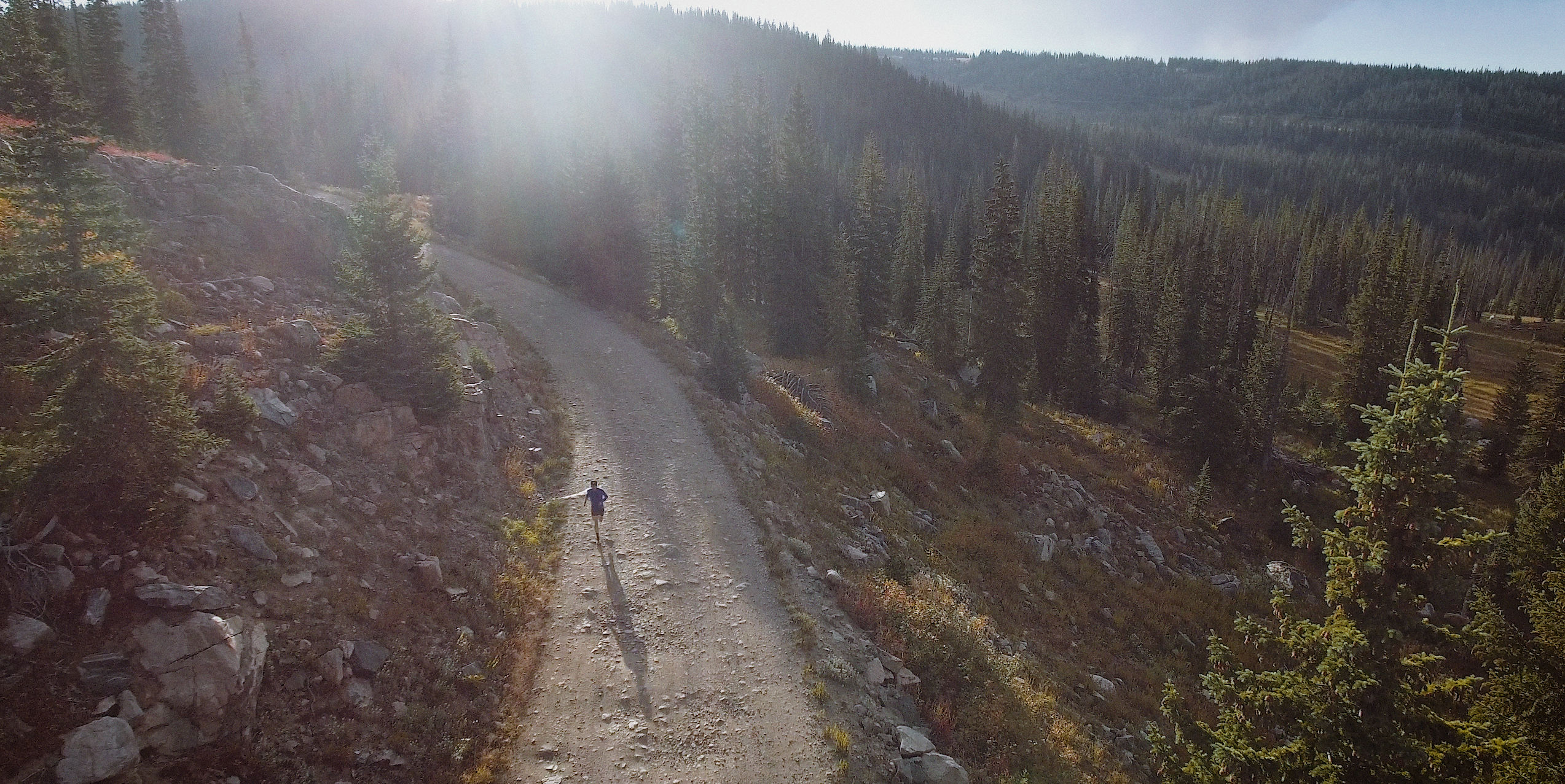 drone photo of man running on dirt road clear summit productions